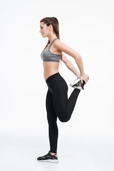 Retrato de vista lateral de una mujer joven fitness de pie y estirando las piernas sobre la superficie blanca