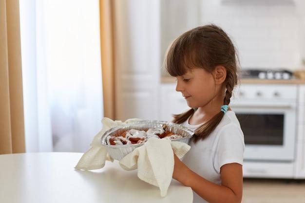 Retrato de vista lateral de niña de cabello oscuro cocinando hornear, despegando del horno de gas y poniendo a la mesa, mirando sonriendo quiere probar un delicioso croissant.