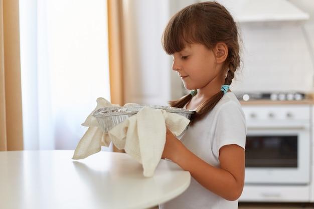 Retrato de vista lateral de una niña de cabello oscuro con coletas de pie en la cocina junto a la mesa con horneado caliente en una toalla de cocina, ayudando a su madre con pasteles caseros.