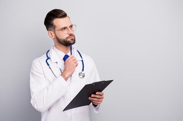 Retrato de vista lateral de perfil de agradable atractivo inteligente inteligente enfocado pensativo doctor barbudo creando estrategia de terapia escribiendo documento de historia de enfermedad aislado en color pastel gris blanco claro