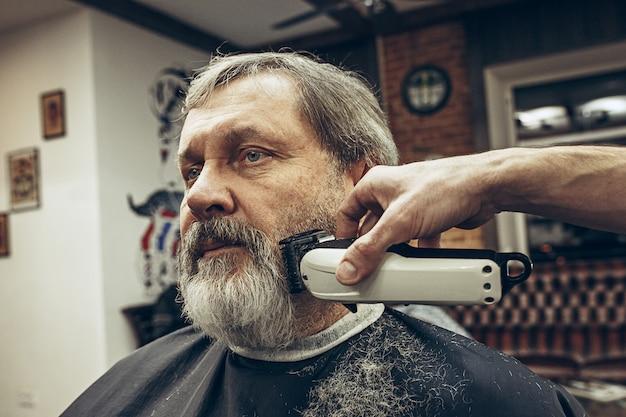 Retrato de la vista lateral del primer del hombre caucásico barbudo mayor hermoso que consigue la preparación de la barba en barbería moderna.