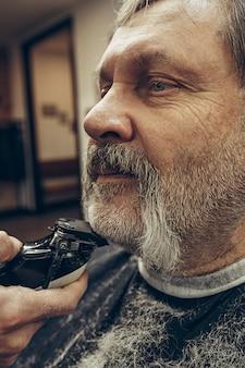 Retrato de vista lateral de primer plano de guapo hombre caucásico barbudo senior conseguir barba aseo en la moderna barbería.