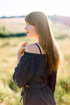 Retrato de vista lateral de la romántica mujer caucásica en ropa negra, caminando en el increíble campo de verano durante el cálido atardecer