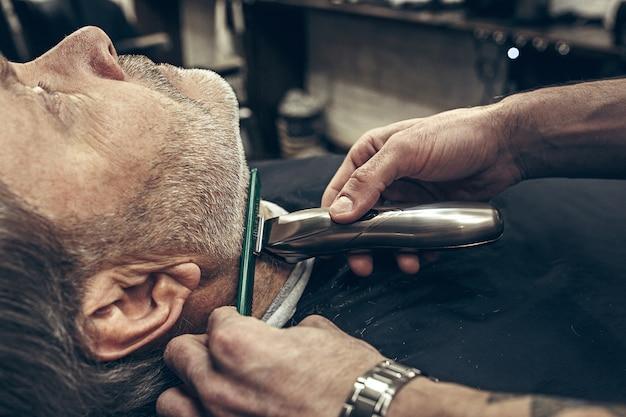 Retrato de vista de perfil lateral de primer plano de guapo hombre caucásico barbudo senior conseguir barba aseo en la moderna barbería.