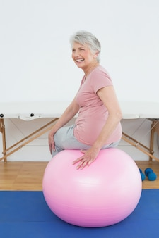 Retrato de la vista posterior de una mujer mayor que se sienta en bola de la yoga