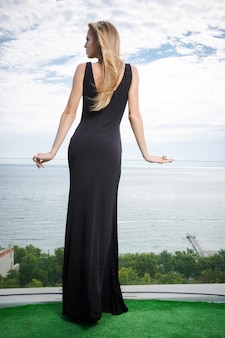 Retrato de vista posterior de una mujer de pie en vestido negro de moda al aire libre con el mar en la pared