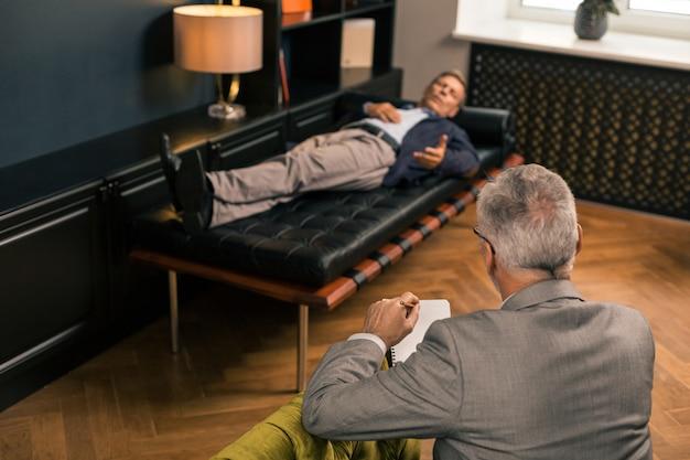 Retrato de vista posterior de un psicólogo profesional sentado en un sillón mientras escucha a un paciente acostado en el sofá