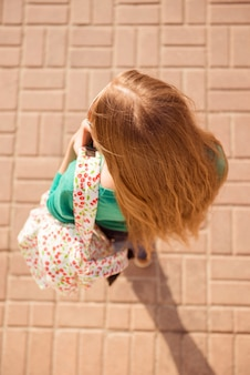 Retrato de vista superior de la joven rubia de pelo largo con mochila