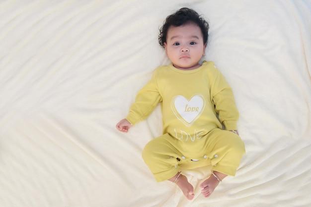 Retrato de vista superior de lindo bebé asiático acostado en la sábana blanca, mira a la cámara