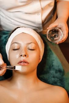 Retrato de vista superior de una mujer encantadora haciendo una máscara anti-edad con ácido hialurónico en un centro de bienestar mientras se apoya en una cama con los ojos cerrados.