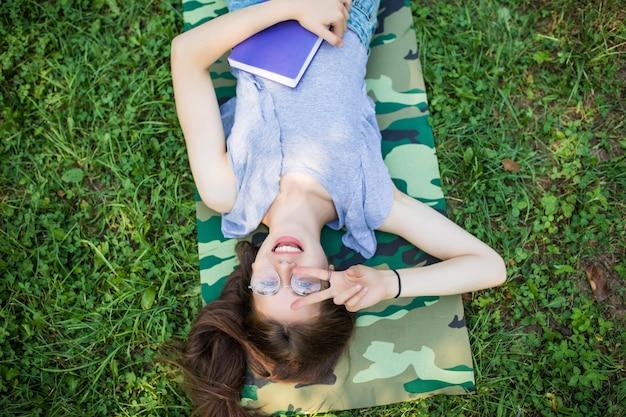 Retrato de vista superior de una mujer joven y bonita relajándose sobre un césped en el parque