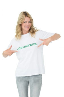 Retrato de una voluntaria mujer feliz apuntando a sí misma