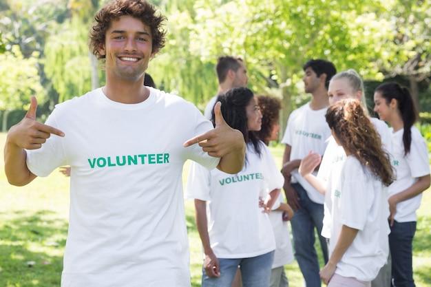 Retrato de voluntario apuntando a la camiseta