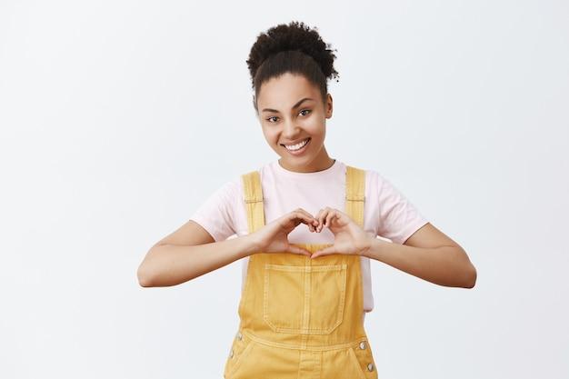Retrato de voluntario de piel oscura encantadora y cariñosa, mostrando gesto de corazón y sonriendo con afecto y simpatía, siendo feliz y alegre, de pie sobre una pared gris
