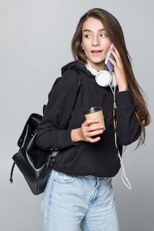 Retrato de un womantalking en un teléfono móvil aislado en la pared blanca