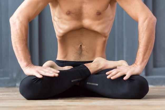 Retrato de yogui hombres respirando y practicando bloqueo abdominal ascendente
