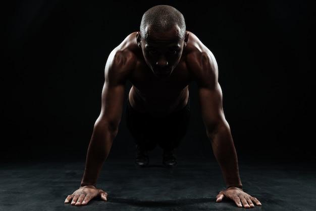 Retrato de youg afroamericano deportista haciendo ejercicio de flexiones