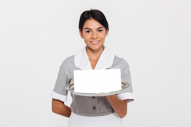 Retrato de ypung sonriente mujer camarero en uniforme con bandeja de metal con invitación vacía mientras está de pie