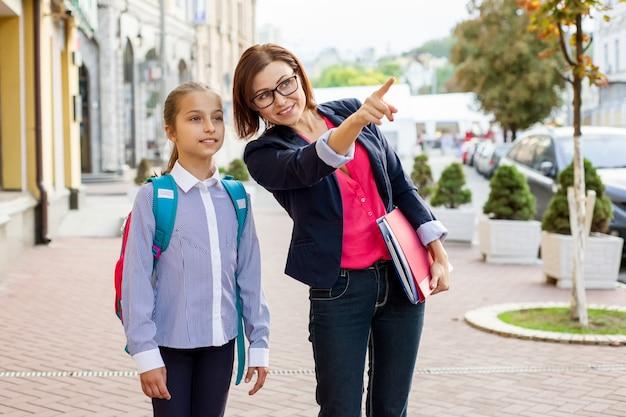 Retratos al aire libre de colegiala y maestra