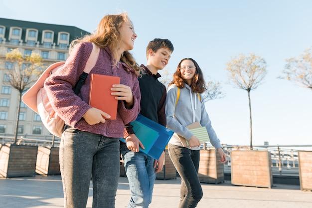 Retratos al aire libre de estudiantes adolescentes con mochilas caminando