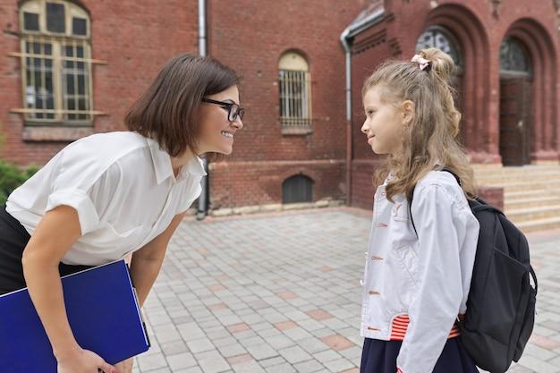 Retratos al aire libre de maestra mujer y niña estudiante juntos