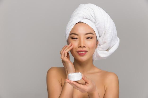 Retratos de belleza hermosa mujer asiática. niña china de pie delante del espejo y cuidando su mirada.