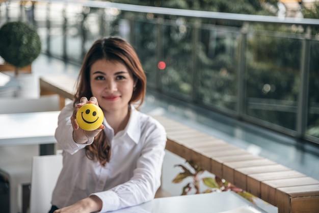 Los retratos de la confianza asiática hermosa de la mirada de la mujer están sosteniendo la bola de la sonrisa mientras que se sienta.