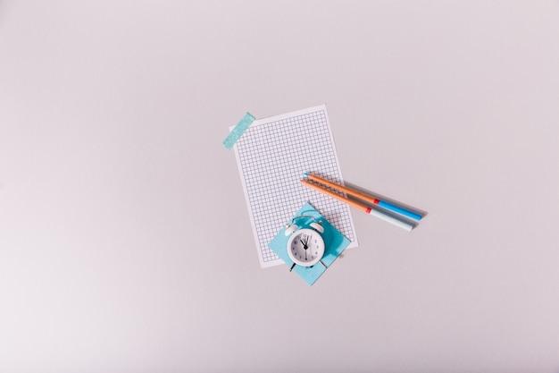Retratos de despertador acostado sobre una hoja de papel pegada a la mesa blanca.