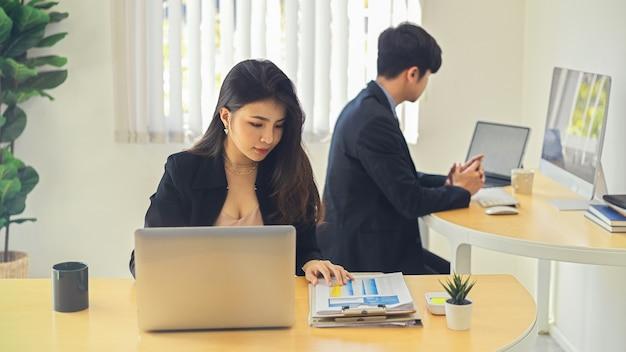 Retratos de dos empresarios que trabajan en su trabajo con suministros de oficina en la sala de oficina moderna