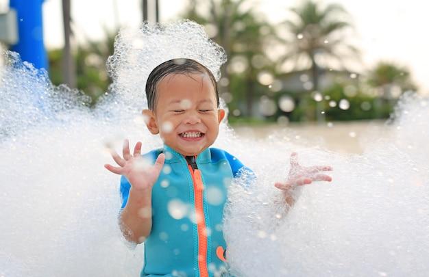 Retratos de feliz pequeño bebé asiático sonriente que se divierte en foam party en la piscina al aire libre.