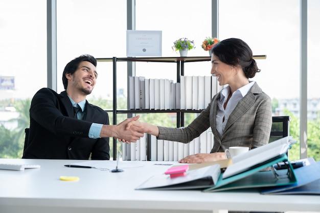 Retratos de hombre y mujer de negocios dándose la mano trabajando en la oficina de finanzas