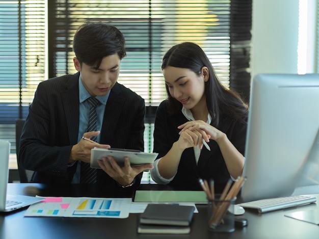 Retratos de jóvenes empresarios que consultan sobre su proyecto con papeleo, tableta y computadora