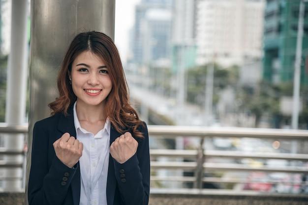 Los retratos de la mujer asiática hermosa parecen alegres y la confianza está de pie y sintiendo el éxito con el trabajo