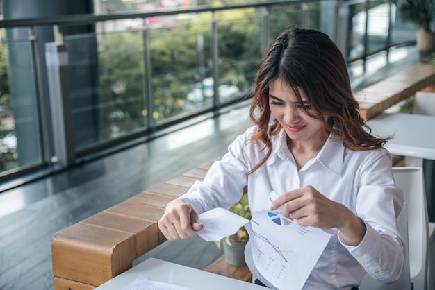 Los retratos de la mujer asiática hermosa son destruyen el documento y la sensación de la carta financiera