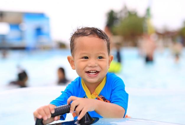 Retratos del pequeño bebé asiático feliz que sonríe divirtiéndose en la piscina al aire libre.