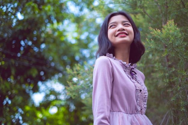 Retratos sonriente joven asiática con pino