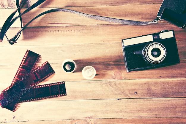 Retro cámara de época y película fotográfica sobre fondo de madera