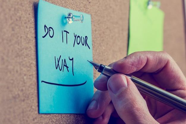 Retro la mano de un hombre sosteniendo un bolígrafo sobre un recordatorio azul con el consejo inspirador de hacerlo a tu manera, clavado en una tabla de madera