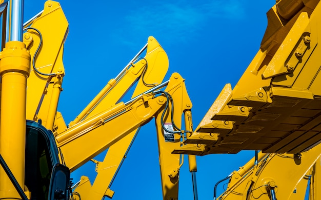 Retroexcavadora amarilla con brazo de pistón hidráulico contra el cielo azul claro.