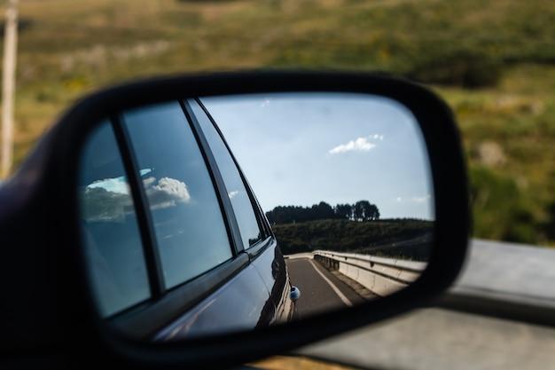 Retrovisor de coche con vista a la carretera.
