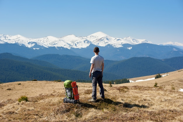 Retrovisor de un hombre admirando la vista de pie en la cima de una montaña con su mochila