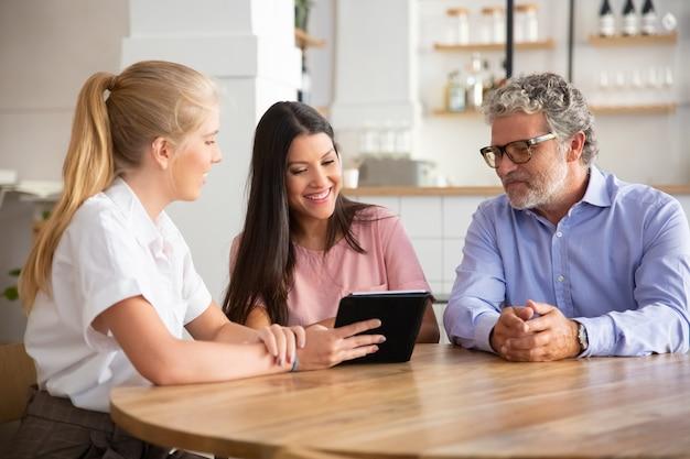 Reunión de agente o gerente femenino con un par de clientes jóvenes y maduros, presentando contenido en tableta