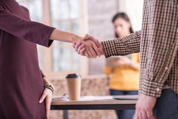 Reunión agradable. apretón de manos amistoso entre buenos amigos positivos mientras se conocen