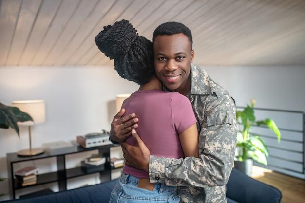 Reunión. atractivo joven afroamericano sonriente en camuflaje abrazando a esposa con peinado alto de pie en casa