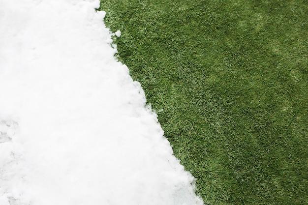 Reunión de cerca la nieve blanca y la hierba verde. entre el fondo del concepto de invierno y primavera.