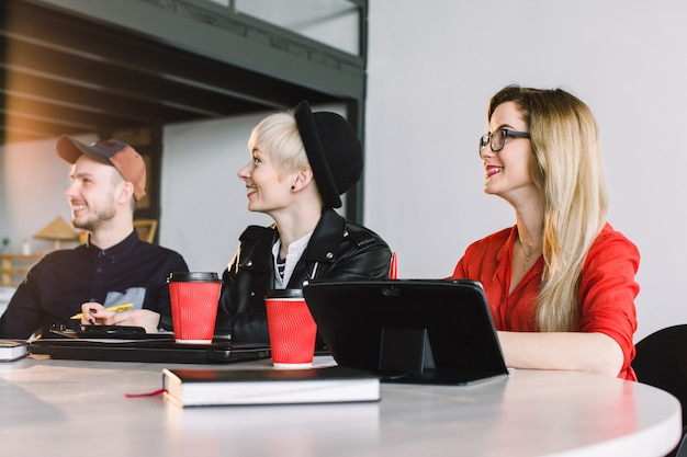 Reunión creativa de la agencia: grupo de empresarios en ropa informal hablando durante la conferencia en la oficina y aplaudiendo durante el discurso
