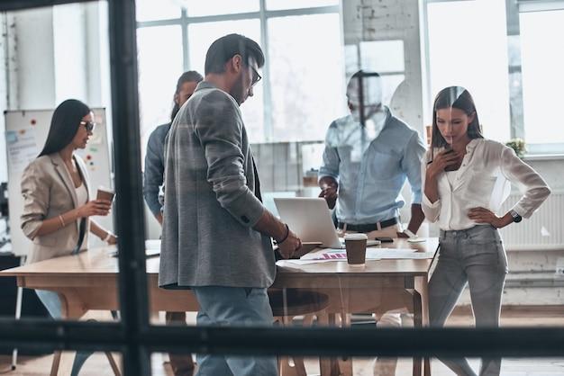 Reunión de día. grupo de jóvenes modernos que trabajan y se comunican juntos mientras están de pie detrás de la pared de vidrio en la sala de juntas