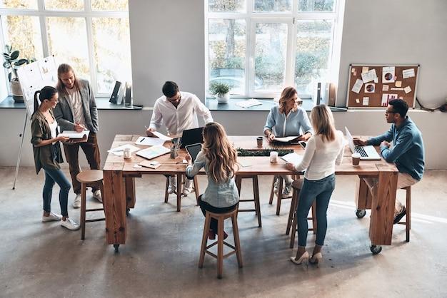 Reunión de día. vista superior de los jóvenes modernos que se comunican mientras trabajan juntos en la sala de juntas