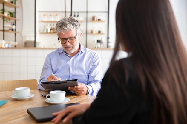 Reunión de empresario maduro centrado con el agente sobre una taza de café en la mujer trabajadora y firma de acuerdo
