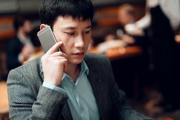 Reunión con empresarios chinos en trajes en restaurante.